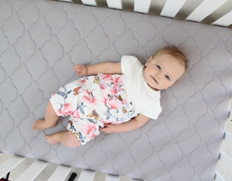 Baby laying on back in crib