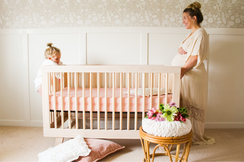 pregnant mom and daughter in baby girl nursery