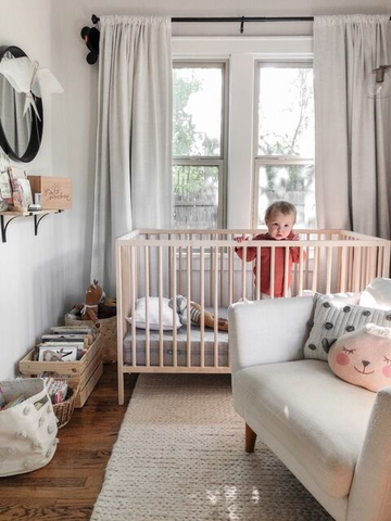 baby girl standing in a crib in a nursery