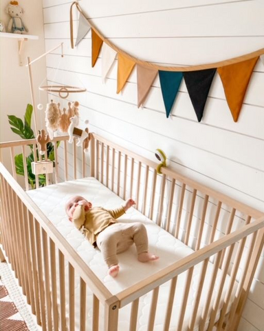 Baby laying in crib in nursery