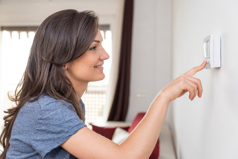 Mom checking thermostat for comfortable temperature for baby