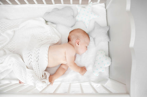 baby sleeping in crib on baby pillows