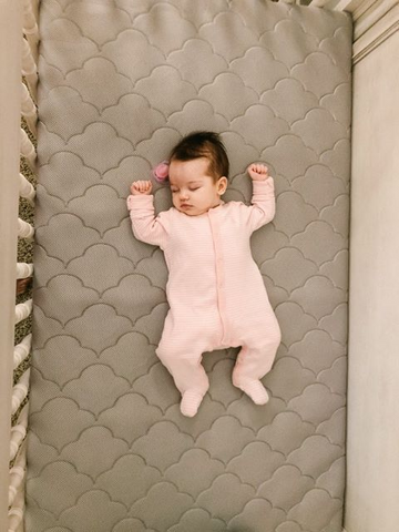 newborn sleeping on crib mattress