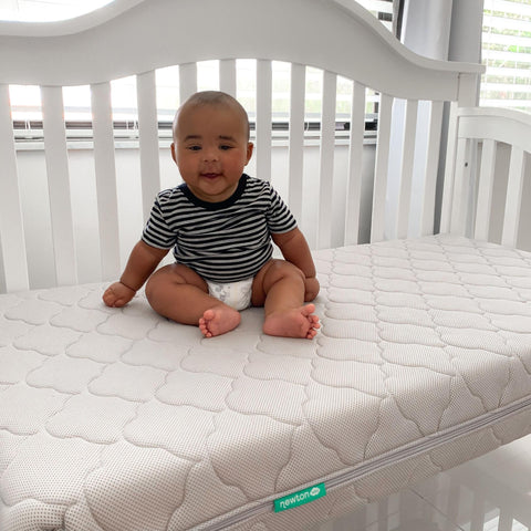 baby sitting up in crib