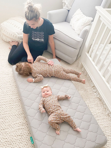 Mom with two babies laying on a Newton Baby crib mattress