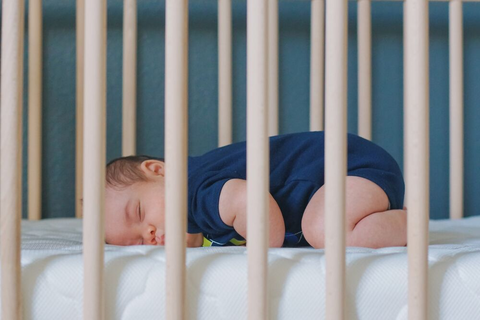 baby sleeping on stomach in crib