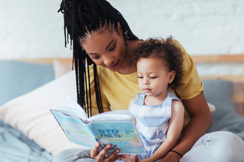 Mom reading to baby before taking her nap