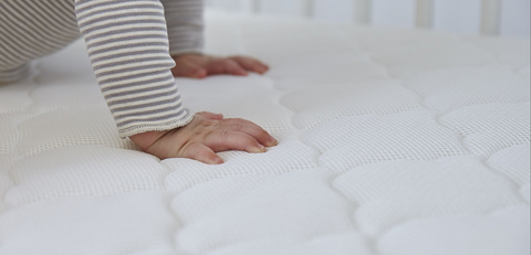 uplcose of baby's hands on bassinet mattress
