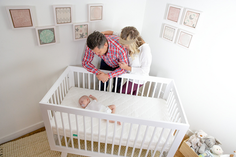 Parents looking down at sleeping baby in crib