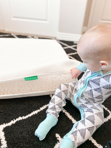 Baby sitting next to a breathable crib mattress
