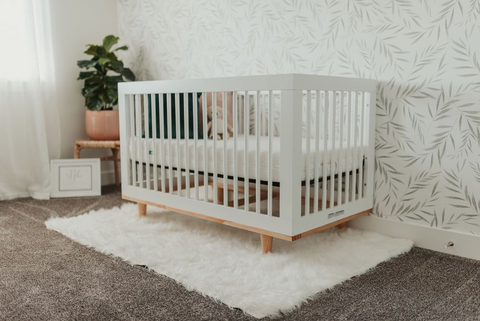 A white crib for twins in a nursery