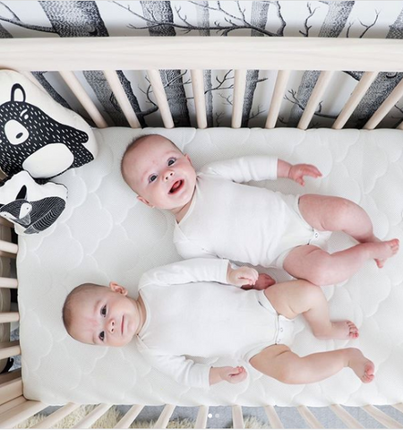 two babies laying next to each other in a crib for twins