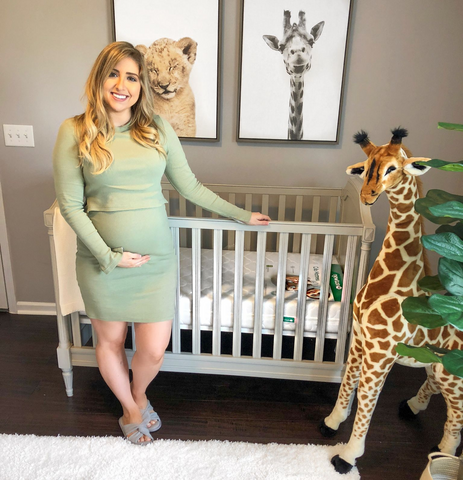 Expecting mom standing next to crib in zoo themed nursery