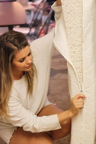 Mom taking cover off crib mattress to clean