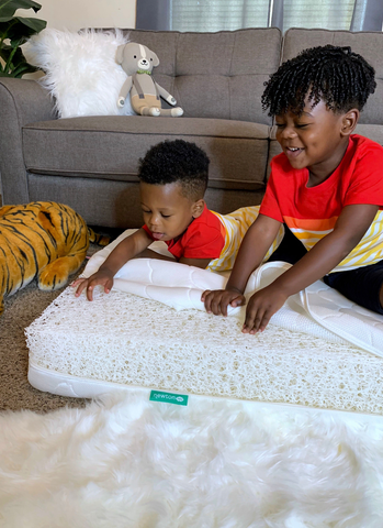 Older sibling helping younger sibling put on crib mattress cover
