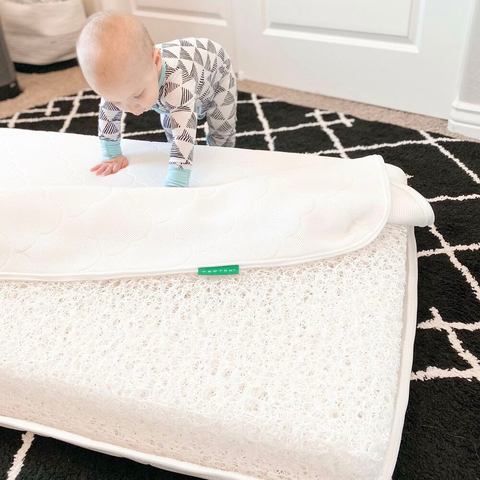 Baby playing with a crib mattress cover