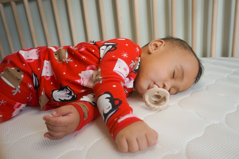 baby sleeping with pacifier and wearing christmas onesie