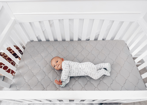 baby laying in crib with proper crib safety