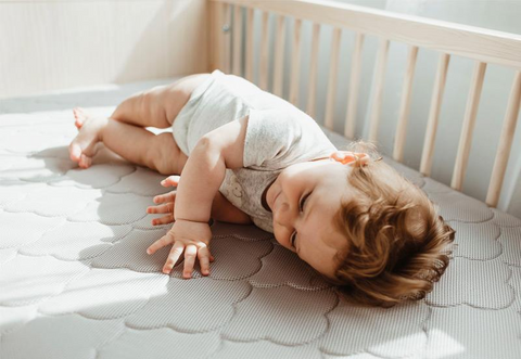 Baby laying on side in crib with changing table