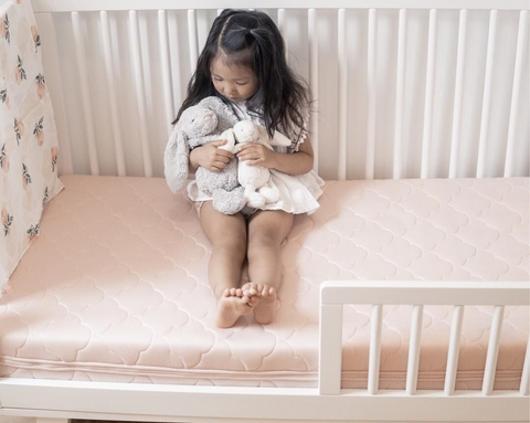 girl playing with stuffed animals while sitting on a toddler bed with a newton baby crib mattress