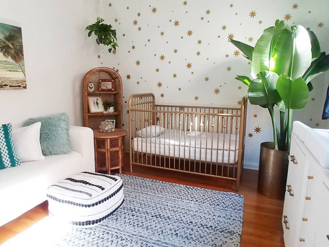 a gender-neutral nursery with gold accents and plants