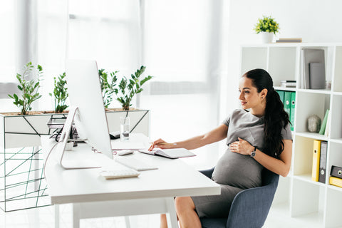 Pregnant mother at desk working