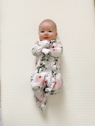 baby wearing cute baby outfit with ruffles and flowers