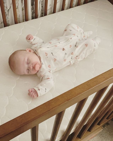 Baby laying in a crib in onesie