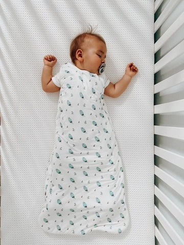 Baby wearing a swaddle blanket to show how to dress baby for sleep