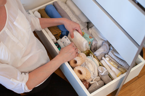Mom putting away clothes after learning how to organize baby clothes