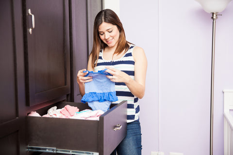 Expecting mom learning how to organize baby clothes