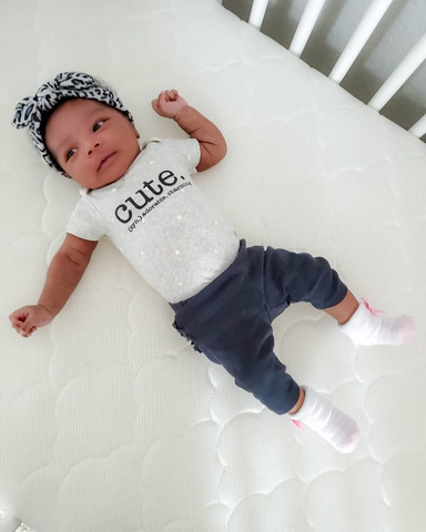 baby laying in crib wearing headband and shirt with word cute on it
