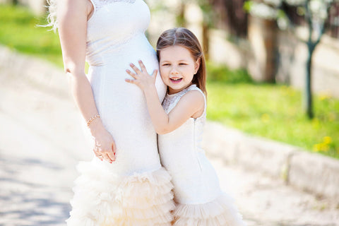 Pregnant mom with daughter hugging her wondering how to prepare for a baby