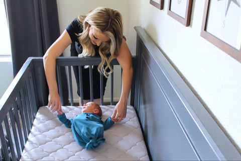 Mom showing how to put a baby to sleep in a crib