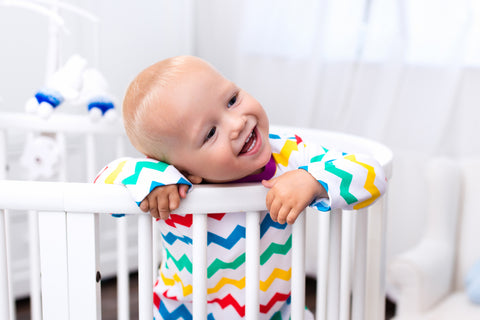 Baby leaning over a mini crib
