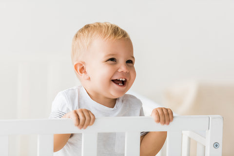 Baby standing in a mini crib