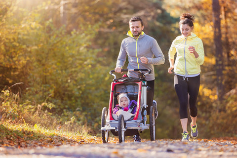 New parents jogging with baby
