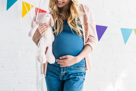 Pregnant mom holding belly at baby shower thinking about newborn gifts