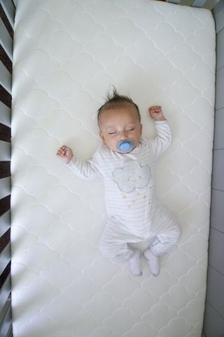 baby sleeping on non-toxic crib mattress
