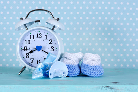 polka dot wall with alarm clock, baby booties, and pacifier