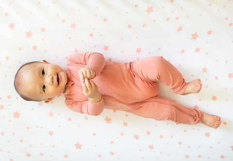 baby in pink onesie laying on back