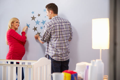 Parents hanging decorations for a perfect themed nursery