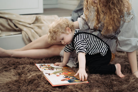 mom and toddler reading a book in the nursery
