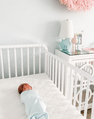 Baby swaddled in crib for perfect baby sleep environment