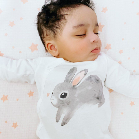 Sleeping baby wearing a onesie with a bunny