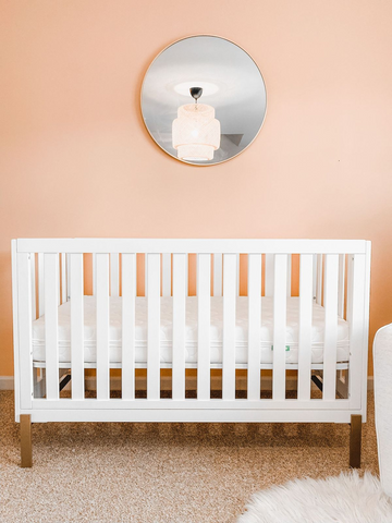 White crib in a nursery with a pink wall
