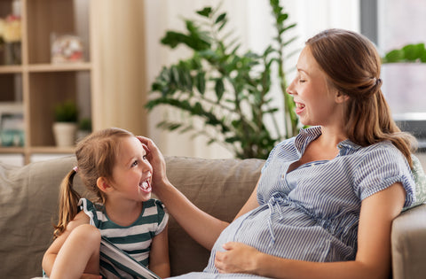 Pregnant mom and daughter on couch laughing.