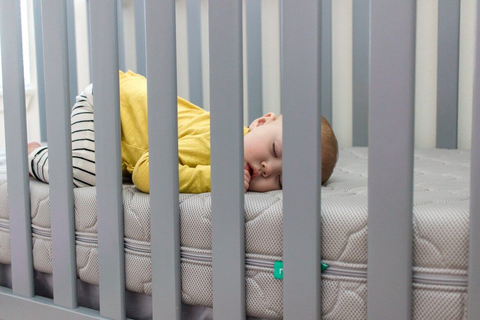 baby sleeping on a newton baby crib mattress in a mini crib