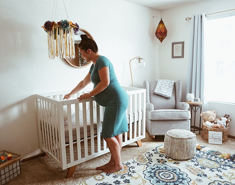 pregnant woman setting up a mini crib in a small nursery