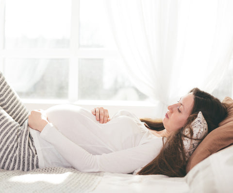 woman in third trimester lying in bed
